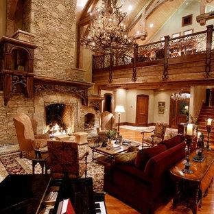 Foto di un ampio soggiorno rustico aperto con sala formale, pareti beige, pavimento in legno massello medio, camino classico, cornice del camino in pietra e nessuna TV