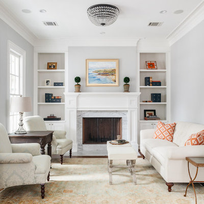 Mid-sized transitional formal and enclosed medium tone wood floor and brown floor living room photo in Houston with a standard fireplace, a stone fireplace, gray walls and no tv