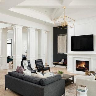 Imagen de salón abierto, clásico renovado, grande, con paredes negras, suelo de madera clara, chimenea tradicional, televisor colgado en la pared, marco de chimenea de madera y suelo beige