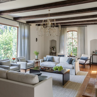 Inspiration for a large transitional open concept medium tone wood floor and brown floor living room remodel in San Francisco with white walls, a standard fireplace, a wood fireplace surround and no tv
