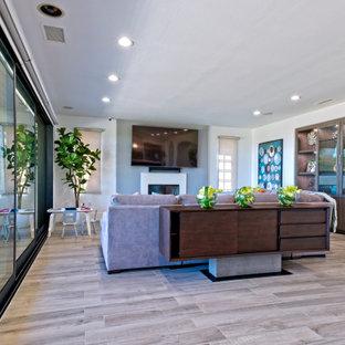 Ispirazione per un grande soggiorno moderno aperto con pareti grigie, pavimento in gres porcellanato, camino classico, cornice del camino in cemento, TV a parete e pavimento beige