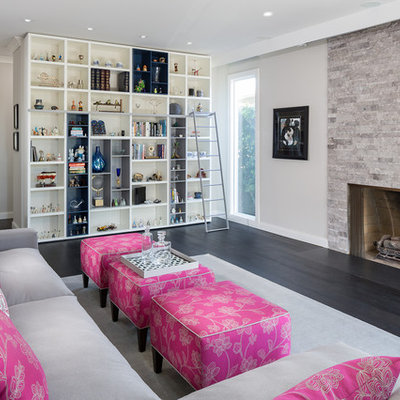 Inspiration for a mid-sized contemporary enclosed dark wood floor and brown floor living room remodel in Los Angeles with beige walls, a standard fireplace, a stone fireplace and no tv