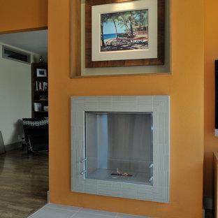 Foto di un soggiorno moderno con libreria, pareti arancioni, pavimento in laminato e cornice del camino piastrellata