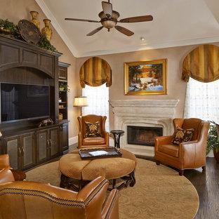 Esempio di un grande soggiorno chic aperto con parquet scuro, cornice del camino in pietra, pareti beige, camino classico, parete attrezzata, pavimento marrone e sala formale