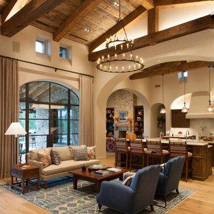 Exemple d'un salon sud-ouest américain avec un mur beige, un sol en bois brun et un sol marron.