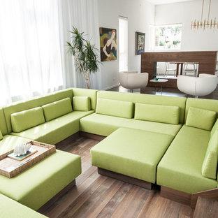 Idee per un soggiorno design di medie dimensioni e aperto con sala formale, pareti bianche, parquet scuro, camino bifacciale, cornice del camino in legno, nessuna TV e pavimento marrone