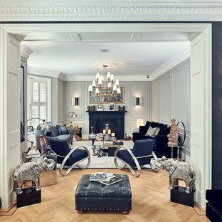 ロンドンの中サイズのトラディショナルスタイルのおしゃれな独立型リビング (グレーの壁、淡色無垢フローリング、標準型暖炉、金属の暖炉まわり、ベージュの床) の写真