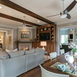 Coastal medium tone wood floor living room photo in Charleston with gray walls, a corner fireplace, a stone fireplace and a media wall