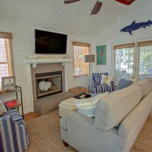チャールストンの中サイズのビーチスタイルのおしゃれなLDK (白い壁、無垢フローリング、標準型暖炉、タイルの暖炉まわり、壁掛け型テレビ、マルチカラーの床) の写真