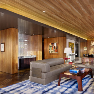 Design ideas for a midcentury open plan living room in Austin with a home bar, brown walls, dark hardwood flooring and brown floors.