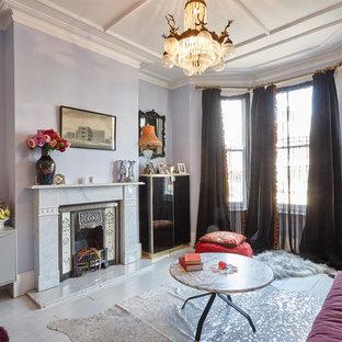 Esempio di un soggiorno vittoriano di medie dimensioni e aperto con sala formale, pareti viola, pavimento in legno verniciato, camino classico, cornice del camino in pietra e TV autoportante