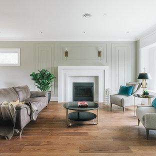 Ispirazione per un soggiorno minimalista aperto con sala formale, pareti verdi, pavimento in compensato, camino classico, cornice del camino in pietra e pavimento marrone