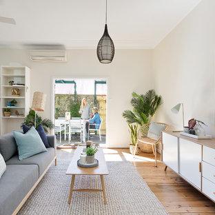 シドニーの中サイズのビーチスタイルのおしゃれなLDK (薪ストーブ、フォーマル、ベージュの壁、無垢フローリング、ベージュの床) の写真