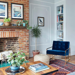 Mid-sized eclectic living room photo in New York with gray walls, a standard fireplace and a brick fireplace