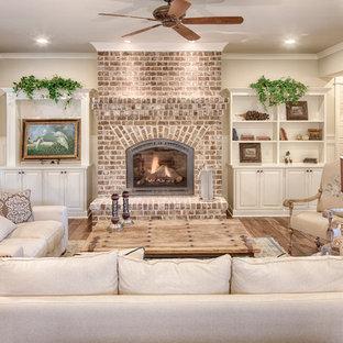 Idee per un soggiorno chic di medie dimensioni e aperto con pareti beige, pavimento in legno massello medio, camino classico, cornice del camino in mattoni e nessuna TV