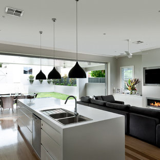 Photo of a large contemporary open plan living room in Sydney with grey walls, medium hardwood flooring, a ribbon fireplace and a wall mounted tv.