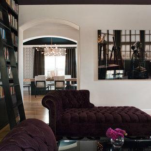 Cette photo montre un salon avec une bibliothèque ou un coin lecture tendance de taille moyenne et fermé avec un mur blanc, un sol en bois clair et un sol beige.