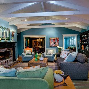 Foto di un soggiorno tradizionale di medie dimensioni e chiuso con pareti blu, pavimento in legno massello medio, camino classico, cornice del camino in mattoni e nessuna TV