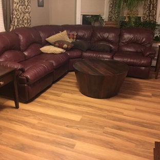 Foto di un soggiorno tradizionale di medie dimensioni e aperto con pareti beige, pavimento in vinile, TV autoportante e pavimento marrone
