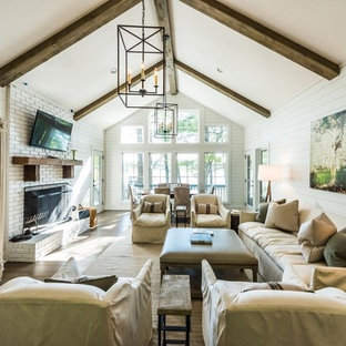 Design ideas for a medium sized farmhouse formal open plan living room in Atlanta with white walls, a standard fireplace, a brick fireplace surround, a wall mounted tv, brown floors and dark hardwood flooring.