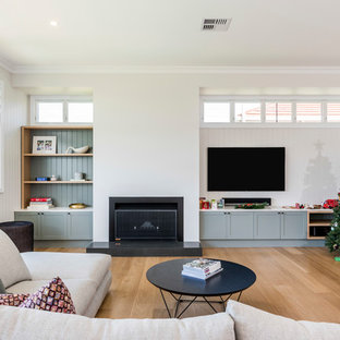 Transitional formal enclosed living room in Brisbane with white walls, medium hardwood floors, a standard fireplace, a wall-mounted tv and beige floor.