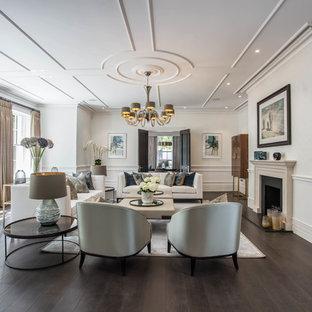 Immagine di un soggiorno tradizionale chiuso con sala formale, pareti bianche, parquet scuro, camino classico, nessuna TV e pavimento marrone