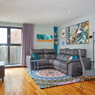 Modelo de salón para visitas abierto, contemporáneo, pequeño, sin chimenea, con televisor independiente, paredes multicolor, suelo de madera en tonos medios y suelo amarillo