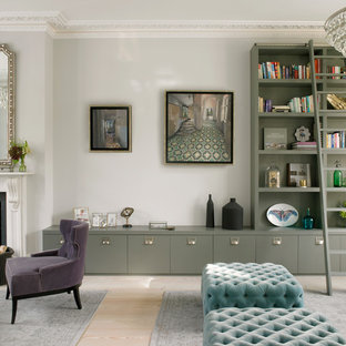 This is an example of a large classic open plan living room in London with grey walls, light hardwood flooring, a standard fireplace, a stone fireplace surround, no tv and beige floors.