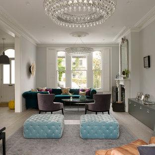 Idee per un grande soggiorno vittoriano aperto con pareti grigie, parquet chiaro, camino classico, cornice del camino in pietra, nessuna TV e pavimento beige