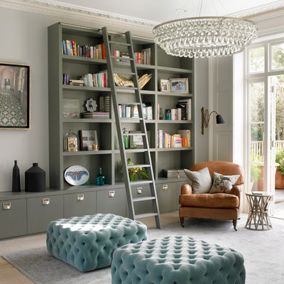Example of a transitional light wood floor living room library design in London with gray walls
