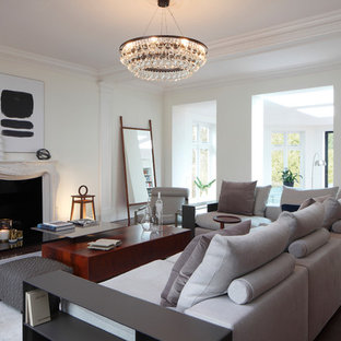 This is an example of a medium sized traditional enclosed living room in London with white walls, dark hardwood flooring, a standard fireplace and brown floors.