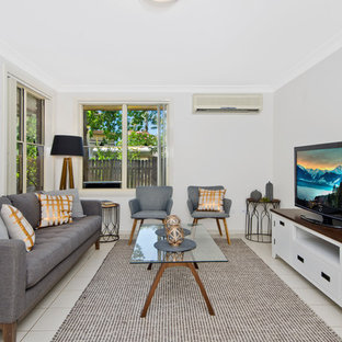 This is an example of a transitional formal enclosed living room in Sydney with grey walls, a freestanding tv and beige floor.