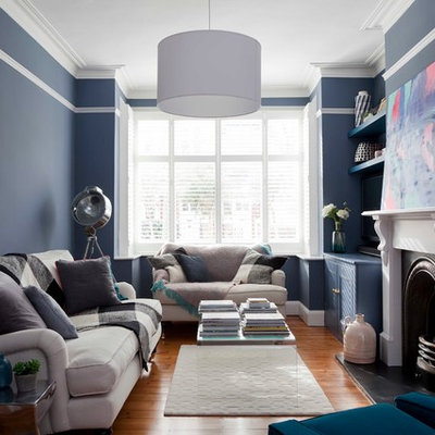 Inspiration for a mid-sized transitional enclosed medium tone wood floor and brown floor living room remodel in London with blue walls, a standard fireplace, a wood fireplace surround and no tv