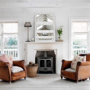 Shabby-Style Wohnzimmer mit weißer Wandfarbe, hellem Holzboden und Kaminofen in London