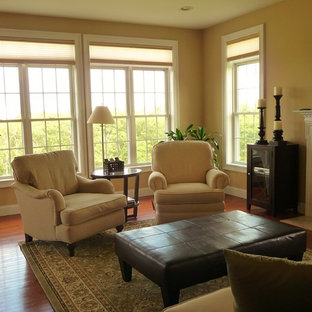 Large elegant open concept medium tone wood floor living room photo in Boston with beige walls, a standard fireplace, a stone fireplace and a wall-mounted tv