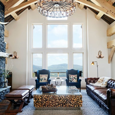 Living room - rustic formal dark wood floor living room idea in New York with white walls and a stone fireplace