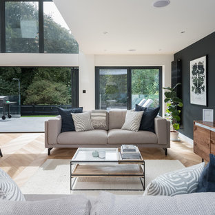 Contemporary open plan living room in Sussex with white walls, a wall mounted tv and beige floors.
