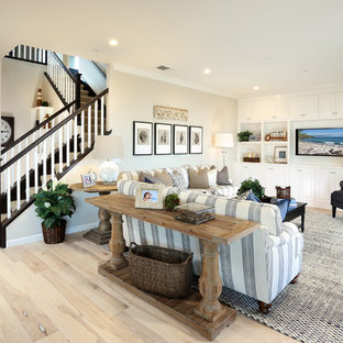 Inspiration for a beach style open concept light wood floor living room remodel in San Francisco with beige walls and a media wall