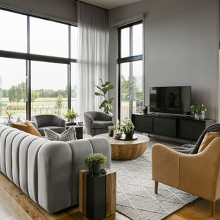 Expansive contemporary open concept living room in Melbourne with grey walls, medium hardwood floors, a freestanding tv and beige floor.