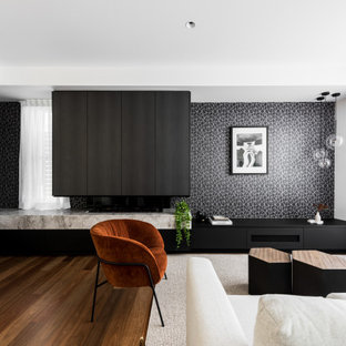 This is an example of an expansive contemporary living room in Brisbane with black walls, a two-sided fireplace and a stone fireplace surround.