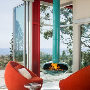 Foto di un soggiorno design aperto con pareti rosse, camino sospeso, cornice del camino in metallo e pavimento grigio