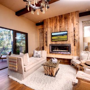 サンフランシスコの中サイズの地中海スタイルのおしゃれなLDK (フォーマル、ベージュの壁、無垢フローリング、横長型暖炉、木材の暖炉まわり、壁掛け型テレビ) の写真