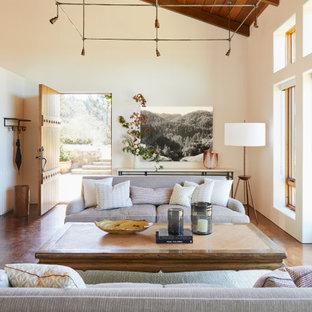 Diseño de salón abierto, abovedado y madera, rural, con paredes blancas, suelo de cemento y suelo marrón