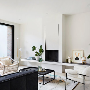 Design ideas for a contemporary formal living room in Melbourne with white walls, light hardwood floors, a standard fireplace and beige floor.