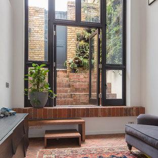 Idee per un piccolo soggiorno industriale aperto con pavimento in mattoni