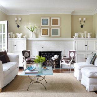 Cette image montre un grand salon traditionnel fermé avec un mur beige, un manteau de cheminée en brique, un sol en bois brun, une cheminée standard et un sol marron.