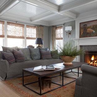 Foto di un soggiorno chic chiuso e di medie dimensioni con pareti grigie, parquet scuro, camino classico, sala formale, cornice del camino in pietra e nessuna TV