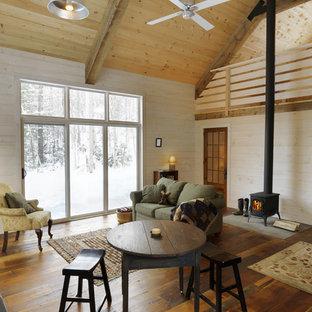 Ispirazione per un soggiorno rustico aperto con pareti beige, pavimento in legno massello medio e stufa a legna
