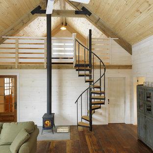 Imagen de salón abierto, rústico, con paredes beige, suelo de madera en tonos medios y estufa de leña