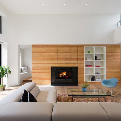 Inspiration for a large scandinavian open concept and formal light wood floor and brown floor living room remodel in Austin with white walls, a standard fireplace, a metal fireplace and a media wall